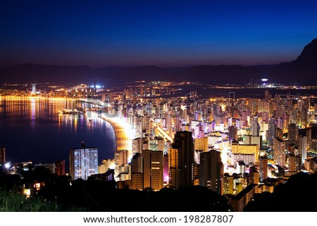 Night city by the sea with an empty beach and beautiful night lighting (Sunset in Spain, Benidorm) - stock photo