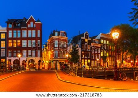 Night city view of Amsterdam canal and bridge, typical dutch houses and bikes, Holland, Netherlands. - stock photo