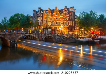 Night city view of Amsterdam canal, bridge and luminous track from the boat, Holland, Netherlands.  - stock photo