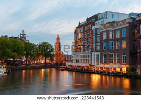 Night city view of Amsterdam canal, bridge and Munttoren tower, Holland, Netherlands.  - stock photo