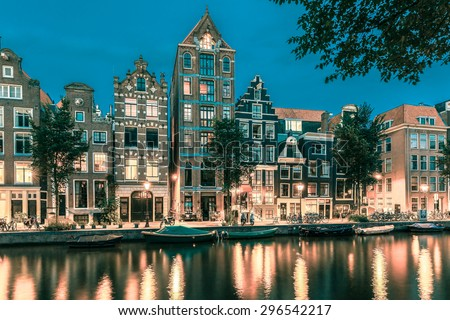 Night city view of Amsterdam canal Herengracht, typical dutch houses and boats, Holland, Netherlands.. Toning in cool tones - stock photo