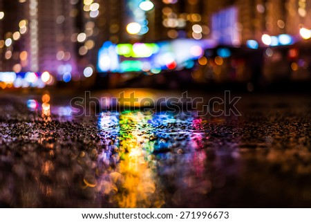 Night cityscape, colored lights reflected in the wet asphalt after rain. View from the level of asphalt - stock photo
