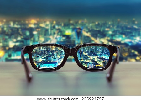 Night cityscape focused in glasses lenses - stock photo