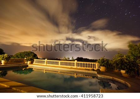 Night cloudscape over the pool in spanish house of Mallorca - stock photo