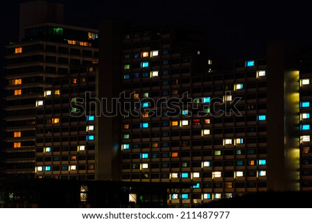 Night colorful windows lights of the high-rise residential building in city sleeping area - stock photo