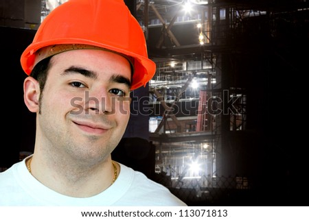Night construction worker smiling in front of an evening job site. - stock photo