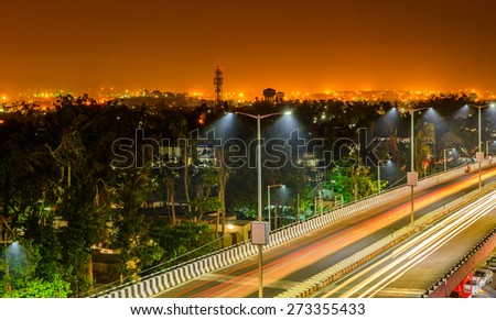 Night freeway with car traffic, lights trails and city lights when long exposed. - stock photo