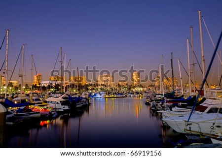 Night Harbor View of Sail Boats and Distant High Riser - stock photo