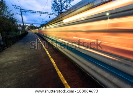 Night high-speed train in motion blur showing light trails in the station - stock photo