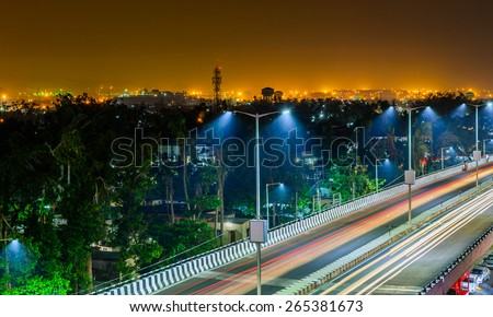 Night highway with car traffic, lights trails and city lights when long exposure, soft focus - stock photo