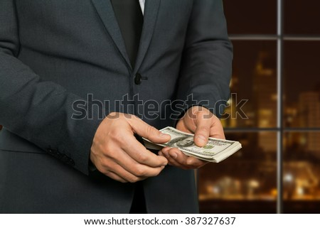 Night hotel manager counting money. Megalopolis businessman counts dollars. Hands of criminal. Far from the law's eyes. - stock photo