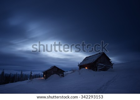 Night landscape in the mountains. Two wooden houses in the mountain settlement. Light in the windows. Path in the snow. Cloudy sky. Carpathians, Ukraine, Europe - stock photo