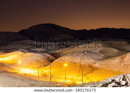 Night landscape of desert mountains near the Dead sea with artificial lighting and a starry sky on the background - stock photo