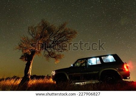 Night landscape on field and terrain car - stock photo