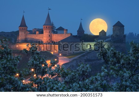 Night landscape with full moon over the fortress. Illumination on a historic building. Historic Landmark - stock photo