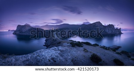 Night landscape with mountains, sea, starry sky and city lights. Amazing view with rocks at dusk in Crimea - stock photo