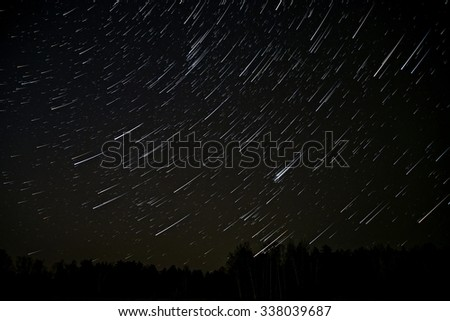 Night landscape with traces of the stars in the night sky on background of a dark forest - stock photo