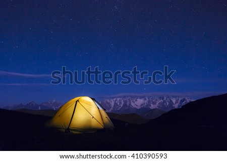 Night mountain landscape with illuminated tent. Mountain peaks and edges night sky with many stars on background - stock photo
