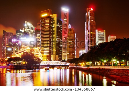 Night panorama of Singapore downtown with reflection in the river - stock photo