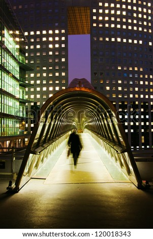 night photography of a pedestrian bridge with glass dome in La Defense, Paris, and a silhouette of a walking businessman - stock photo
