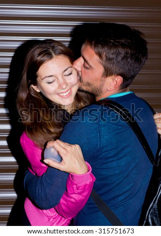 Night portrait of happy Couple at chocolate urban wall background.Portrait of cheerful and lovely couple.So happy. Beautiful young boyfriend with beard kissing girlfriend and she closed her eyes. - stock photo