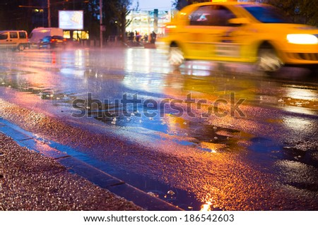 Night rain in the city with rain drops and taxi - stock photo