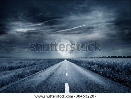 Night road against the background of cumulus clouds - stock photo