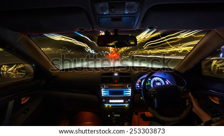 Night road view from inside car natural light street and other cars is motion blurred - stock photo