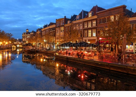 Night scene in Leiden, The Netherlands with old houses along the Nieuwe Rijn Canal. - stock photo