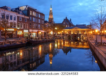 Night scene in Leiden, The Netherlands with the Korenbeursbrug bridge and the City Hall (Stadhuis). - stock photo
