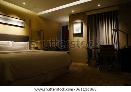 Night scene in luxury hotel room, nightstand with lamp. - stock photo