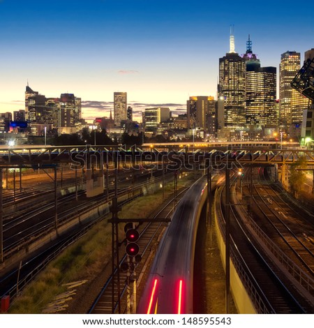 night scene of an electric train heading towards Melbourne - stock photo