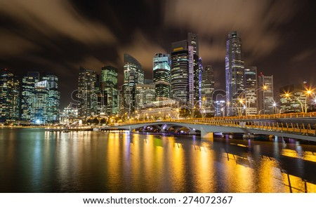 Night scene of Singapore cityscape showing the newly built Jubilee Bridge linking Merlion Park and the waterfront promenade in front of Esplanade. - stock photo