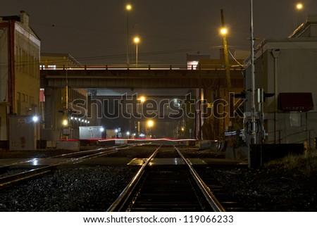 Night scene of train tracks in the rain. - stock photo