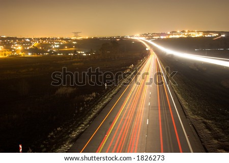 Night scene with city background over busy highway - stock photo