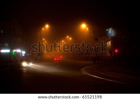 Night scene with moving cars and walking people in the fog - stock photo