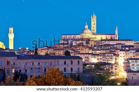 Night scenery of Siena, a medieval town in Tuscany Italy, with view of the Dome & Bell Tower of Siena Cathedral ( Duomo di Siena ) and landmark Mangia Tower ( Torre del Mangia ) in evening twilight - stock photo