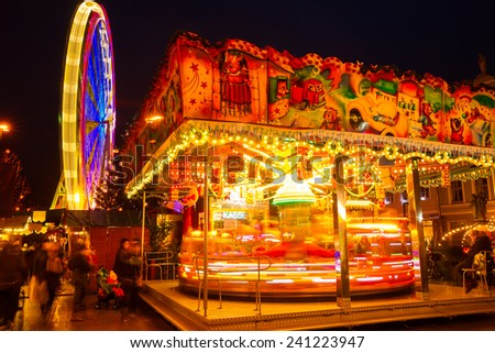 Night shot of a ferris wheel and carousel in Cottbus christmas market - stock photo