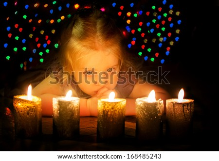 Night shot of the baby girl with candles with beautiful bokeh at background - stock photo