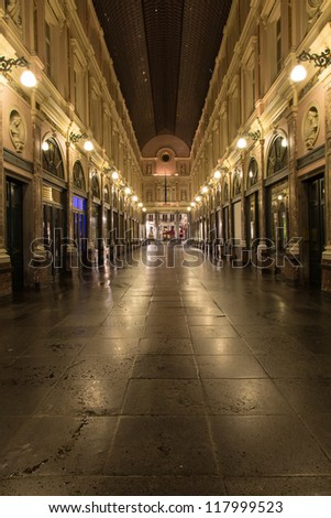 Night shot of the famous luxury shopping mall in Brussels, Belgium, the Galeries St Hubert, with characteristic symmetrical shot with lights in converging lines - stock photo