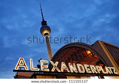Night shot of the train station Berlin Alexanderplatz with the famous TV tower  in the background. - stock photo