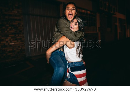 Night shot young woman lifting her best friend laughing. Female friends hanging out and having fun. - stock photo