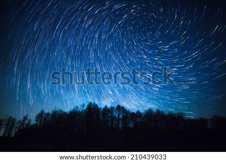 night sky, spiral star trails and the forest - stock photo