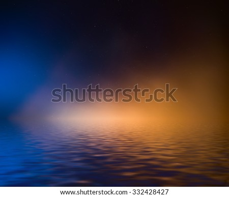 Night sky with colorful cloud and stars reflected in water. - stock photo