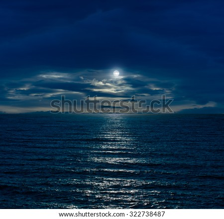 Night sky with full moon and reflection in sea and clouds - stock photo