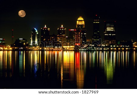 Night skyline of Louisville Kentucky over the Ohio river with the full moon. Horizontal orientation. - stock photo