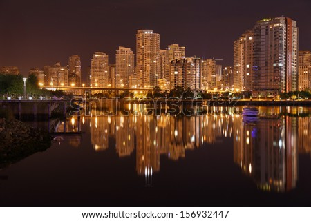 Night Skyline, Vancouver, British Columbia. Condominiums reflect in the calm waters of False Creek at night. Vancouver, British Columbia, Canada.  - stock photo