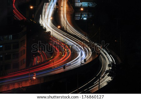 Night skyline view of city and highways with flowing traffic - stock photo