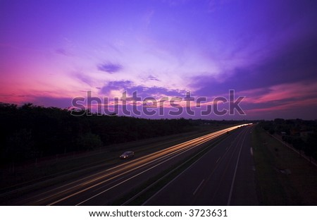 Night, sunset,  shot of a hungary autobahn, highway, long time exposure, motion blured car lights - stock photo