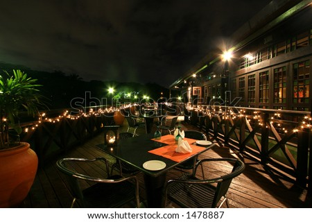 Night time on a verandah at a lake-side bar at a Kuala Lumpur resort hotel - stock photo